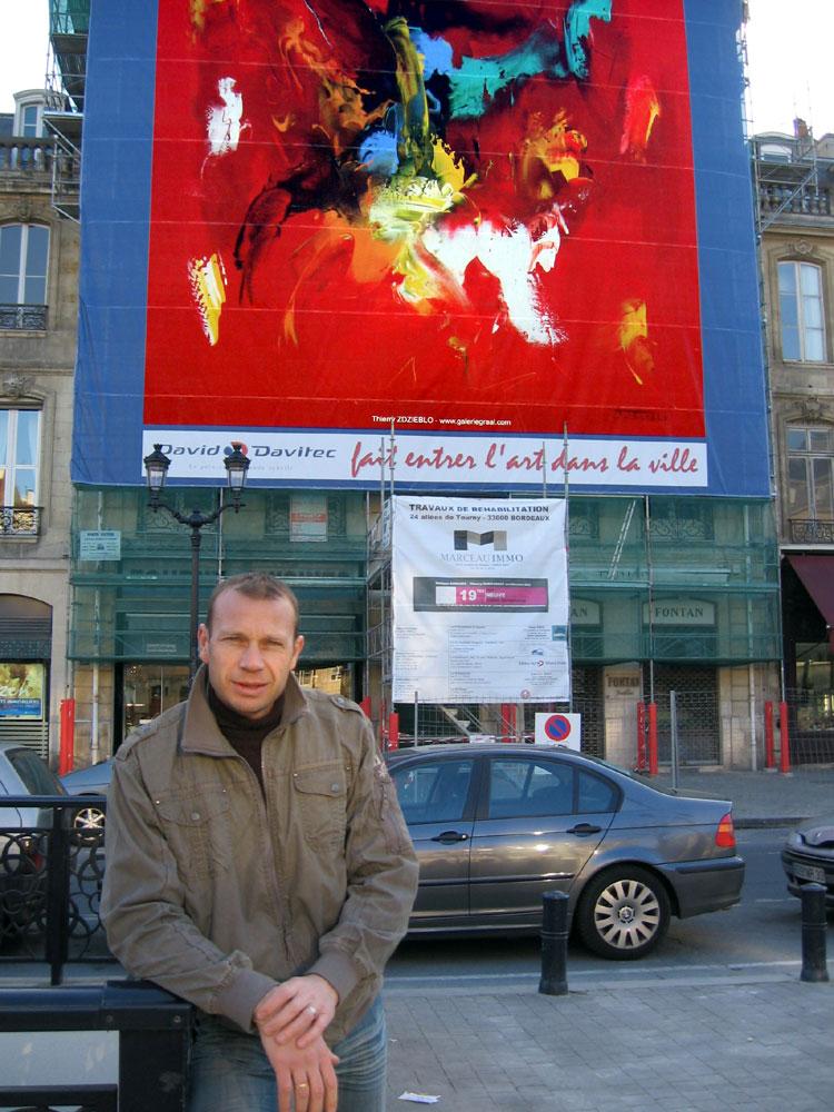 Thierry ZDZIEBLO devant une reproduction de son oeuvre